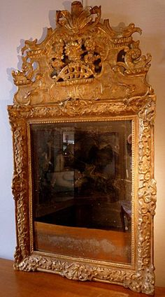 Fine, French, Regence period mirror: In solid, carved giltwood with original surface and original mercury glass.