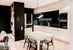 Biało czarna kuchnia z kamiennym granitowym blatem, połączona z salonem, którego ozdobę stanowi niesymetryczny regał na książki połączony z niską komodą.