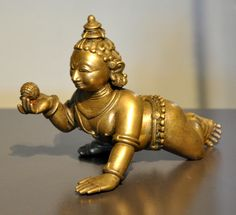 A bronze sculpture of Krishna as child holding a ball of butter from Odisha, circa Photo by Andreas Praefcke. US Public Domain via Wikimedia
