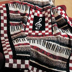 Beautiful Voices  Quilt Designed by Gail Kessler.  Made by Louise Horkey.  Machine Quilted by Judy Castleman.    Red, black, and cream prints join in perfect harmony in this music lover's quilt. Preprinted rows of singers and piano keys surround a machine-appliquéd treble clef.