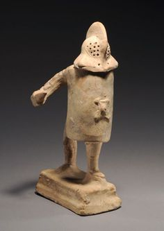 Roman terracotta Murmillo gladiator, 1st-2nd century A.D. Wearing removable, crested helmet with inset triangular visor carrying an oblong shield and dagger, a large greave on his advancing leg, 24.5 cm high. Private collection