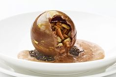 A bittersweet chocolate sphere filled with banana caramel, banana frozen yogurt, and candied sunflower seeds set on top of a banana-sunflower seed cake and served with a warm chocolate sauce poured table side. [no recipe]