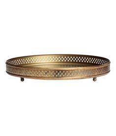 Kulta. Pyöreä metallitarjotin, jossa reikäkuvioinen reuna. Pyöreät, pienet jalat. Korkeus 4,5 cm, halkaisija 30 cm.