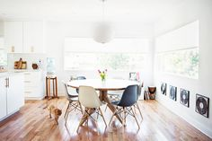 A light-drenched midcentury modern dining space with wood floors, a round dining table, Eames plastic chairs, and a paper lantern