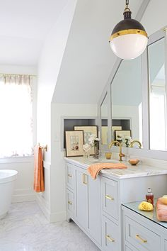 Bright bathroom with brass fixtures and neutral painted cabinetry.