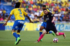 Lionel Messi of Barcelona holds off the challenge from Las Palmas' Jonathan Viera during the La Liga match between UD Las Palmas and Barcelona at Estadio de Gran Canaria on May 14, 2017 in Las Palmas, Spain.
