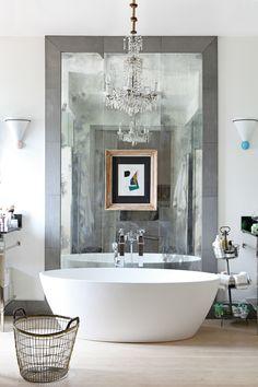 El baño - AD España, © Asier Rua Sobre una pared de cristales envejecidos, Collage de Gerardo Rueda comprado en Candelabro. La lámpara de cristales es del anticuario Agurcho Iruretagoyena.