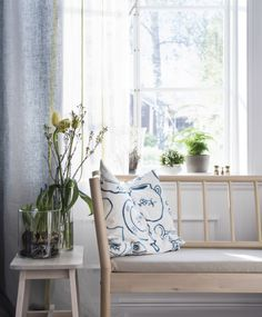 Nærbilde av en benk og blomster foran et åpent vindu med sol.