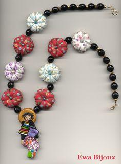 Collier avec pendentif en pâte polymère, coussins en tissu et perles en verre.