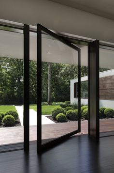 This large black-framed, pivoting glass door provides access to the backyard without blocking the view. #PivotingGlassDoor #Door #PivotingDoor