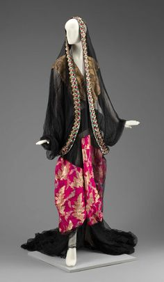 Museum of Fine Arts, Boston. Traditional Najdi dress, Saudi Arabia.  Thawb made of black netting with gold and silver embroidery at headpiece and pink and gold floral panel sewn in. Bottom trim of green, gold, and pink sequins.