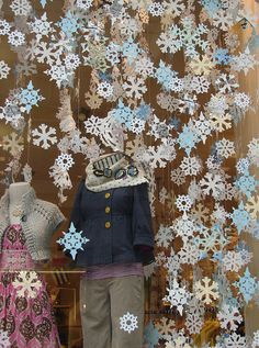 Love the paper snowflakes in this Anthropologie holiday window display. #paper #retail #merchandising #display #snowflakes #Christmas