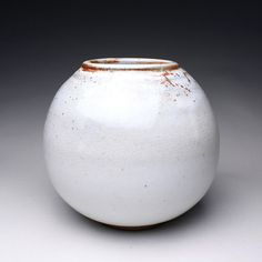 This handmade stoneware vase is glazed with several layers of shino glaze on the outside and a light rusty orange shino inside. Measures 8 tall x