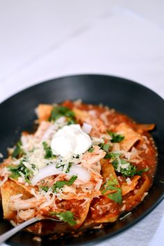 """""""Literally one of my favorite reciped I've blogged: Chipotle Chicken Chilaquiles. Crispy corn chips simmered with a chipotle salsa. Then topped with shredded chicken, sour cream, red onions, and cilantro. Recipe from ThatSquarePlate.com"""