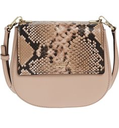 Scratch-resistant crosshatched leather and snake-embossed contrast trim add interesting visual texture to  this structured saddle bag by Kate Spade.
