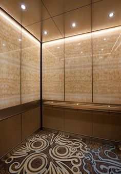 LEVELe-105 Elevator Interior with upper panels in ViviStone Honey Onyx glass with Standard finish; lower panels in Bonded Bronze with Natural Patina and Rain pattern; Rectangular Handrail in Satin Bronze at the InterContinental Dallas, Dallas, Texas
