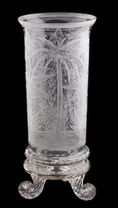 An engraved glass cyndrical footed vase, probably English, 19th century, with exotic palms on scrolled feet.