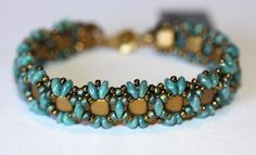 Beadwoven Peekaboo bracelet of Teal Superduo beads, Matte Gold Tile Beads, and green and bronze seed beads, in my original pattern. Measures