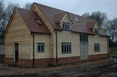 Border Oak - Weatherboarded barn style home under construction.