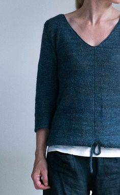 Blue tunnel is a slightly oversized, v-neck sweater with a center faux seam and drawstring hem.