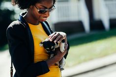 A candid picture of a woman outdoors holding a puppy