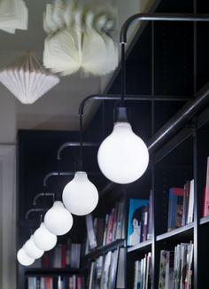 Lutyens & Rubenstein, London bookshop in Notting Hill, book sculptures hanging from ceiling, black book shelves, detail of modern globe pendants