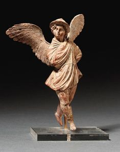 A GREEK TERRACOTTA FIGURE OF EROS   hellenistic period, circa late 3rd-early 2nd century b.c.   Depicted with outstretched wings, his helmeted head turned to the right and slightly raised, his arms wrapped tightly in a himation, the left arm bent, his hand on his hip, the right arm bent at the elbow, his hand at his chest, with traces of blue pigment for the himation
