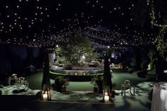 Dark lighting scheme with a starlit ceiling during dinner. Marquee over a lawn with a sunken garden, using an existing round hedge in the middle to create a bar. Flora Soames interior designer
