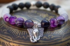 Purple Agate round beads - Black Lava Stone round beads - White quartz round beads - Silver tone spacer beads - Silver tone Elephant charm - 7 Inches un-stretched (approximately). These bracelets best fit people with a medium frame. - Ships from Canada.  The beautiful elephant charm rests between symmetrical patterns of swirling purple agate beads, white quarts, and finally lava stone. Perfect for yoga, meditation, and ...