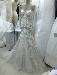 Steven Khalil fit and flare wedding dress with no straps, sweetheart neckline, princess seams, all over lace appliques, and tulle skirt with lace applique accents.
