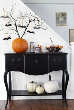 Dark Arts: Perk up the foyer with a bevy of fluttering bats. Simply stick backyard branches into a plain pumpkin and hang a few spooky ornaments. Click through for more pumpkin decorating ideas!