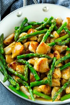 Chicken and asparagus stir fry in a savory brown sauce.