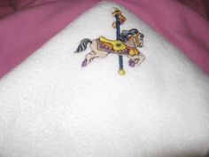 Baby will love to cuddle up on this soft white plush fleece baby blanket with a embroidered carousel horse The baby carousel blanket can be used in the crib bassinet Embroidered Baby Blankets, Fleece Baby Blankets, Pacifier Holder, Baby Burp Cloths, Baby Hair Bows, Carousel Horses, Custom Embroidery, Washing Clothes, Cuddling