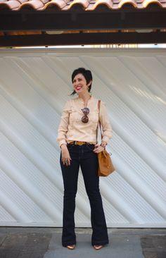 camisa rosê com drapeados e frufrus, calça flare jeans escura, scarpin dourado, bolsa saco caramelo