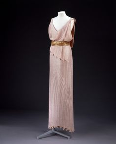 """Evening Dress: Jean Patou (1880-1936): 1932-1934, tulle and hand-sewn sequins. """"This long sleeveless evening dress made of tulle is entirely covered in pink sequins. The bodice is loosely draped and has a slightly pleated peplum at the front. There is a golden sequinned belt at waist level. The skirt of the dress is tubular and ends at the bottom with a trompe-l'oeil effect of pleats."""""""