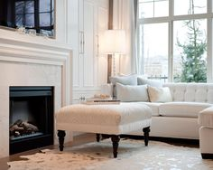 I love everything about this living room, the white couch with greyish blue pillows, the ottoman, fireplace.... <3
