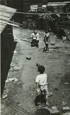 戦後まもない1947年(昭和22年)。 路地裏で楽しそうに野球をする母子です。