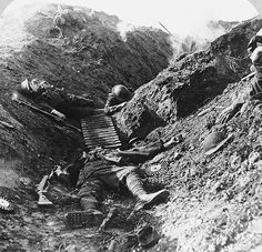WW1: British troops lie dead in their trench following a German counterattack and artillery barrage. Note the ammo drums for the Lewis Light MG on the ground on both sides of the KIA in the center of the photo.