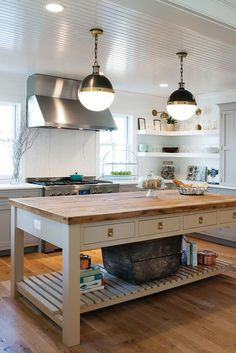 A pair of Hicks Pendants hang over a freestanding gray kitchen island fitted with drawers adorned with unlacquered brass recessed hardware topped with butcher block.