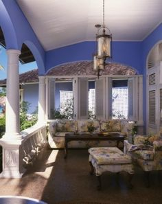 Love the color! A formal seating arrangement for this porch. Columns and shutters are beautiful.