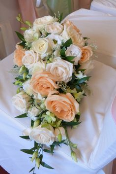 Trailing bridal bouquet of ivory and peach 'avalanche' roses, 'vendela' roses…