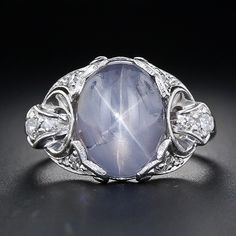 A shimmering bluish-grey star sapphire, weighing 8.00 carats, is the central focus of this artfully sculpted Art Deco ring, beautifully crafted in platinum, circa 1930s. Direct incandescent lighting ignites a dynamic six-legged star on top of the gemstone, which in gemological parlance is known as asterism. The graceful and multi-dimensional platinum mounting twinkles with a quarter-carat of small round diamonds. A delightfully distinctive and original vintage star sapphire ring.