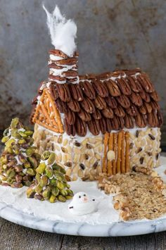 """A rustic christmas gingerbread house made using nuts! Learn how to make a gingerbread house out of a butter box, plus tons of decorating ideas and the best gingerbread 'glue'! I would totally do the house as a """"cheeseball"""" then cover it with the nuts Cool Gingerbread Houses, Gingerbread House Designs, Gingerbread House Parties, Gingerbread Village, Christmas Gingerbread House, Rustic Christmas, Gingerbread Cookies, Gingerbread House Decorating Ideas, Italian Christmas"""