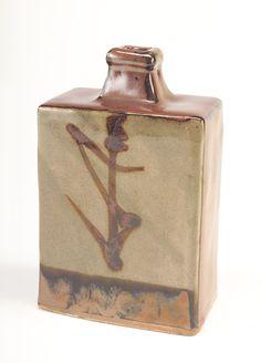 SHOJI HAMADA (Japanese, 1894-1977) Fine and early stoneware square bottle, c. 1955-60, yellow slip ground with iron brush sugarcane motif and clear overglaze; kaki glaze around collar and base.