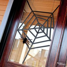Use painters tape or electrical tape to make a spiderweb for a window.