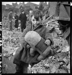 Abandoned boy holding a stuffed toy animal amid ruins following German aerial bombing of London, 1945.
