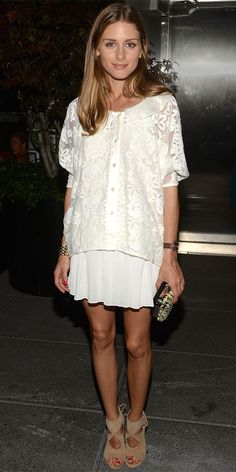 OLIVIA PALERMO The ever-stylish Olivia Palermo went monochromatic in an ivory lace blouse and stark white pleated skirt, save for a printed clutch and her beloved neutral Aquazurra cut-out booties.