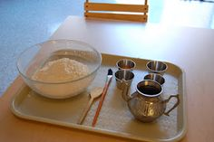 Bread baking for toddlers. A tray helps define the work space. A bowl of 2 1/2 cups of whole wheat flour, every ingredient in a separate bowl and a pitcher that is just the right size. Once the ingredients are mixed, the child can brush his hands and the tray with oil for an added sensory experience before kneading the dough.