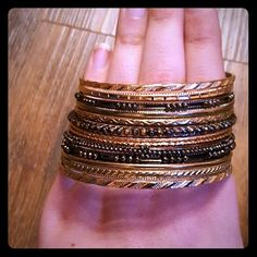 """Elegant Bangle Set Set of 13 bangle bracelets: 4 black and 9 gold. Each has a unique design that complements the others. 2 and 3/4"""" in diameter. Liz Claiborne Jewelry Bracelets"""