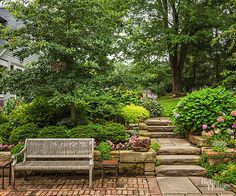 Common bricks fashion a fetching foundation for a sunken patio reached via stone steps and a stone-paved path. Bricklayers created one-brick-wide bands that alternate direction to create a simple pattern that intensifies the patio's charm.